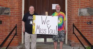"""Towngate Theatre staff hold a sign that says, """"We Miss You."""""""