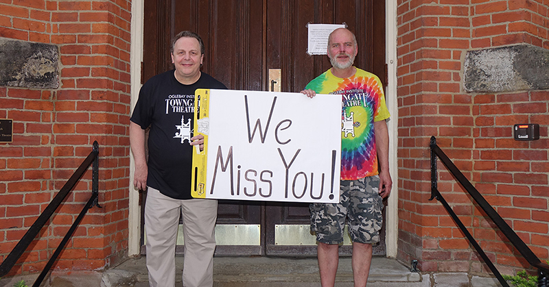 "Towngate Theatre staff hold a sign that says, ""We Miss You."""